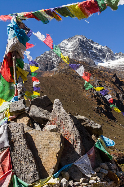 Prayer Flags And Mani Stones Sit In Front Of Khumbila, A Sacred Sherpa Mountain In Nepal's Himalayas