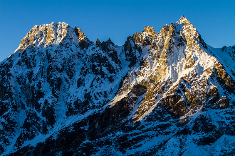 Jagged peaks are bathed in morning sun light in the Himalayas near Gokyo, Nepal