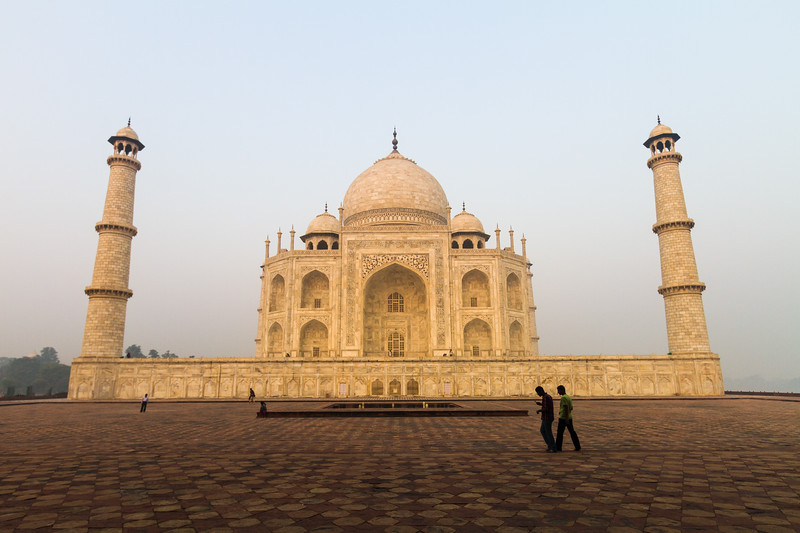 The Taj Mahal an minarets as seen from the side before sunrise with people walking in front