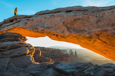 A lone man stands atop Mesa Arch in Canyonlands National Park as the rising sun illuminates the bottom of the arch.
