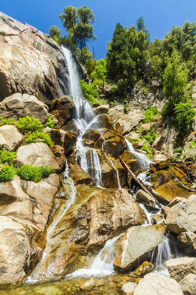 Cascading waterfall in Kingss Canyon National Park, California, on a sunny day with blue skies.