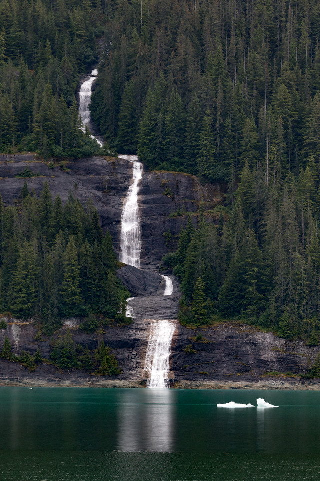 A waterfall in Alaska plummets to the icy waters of a bay