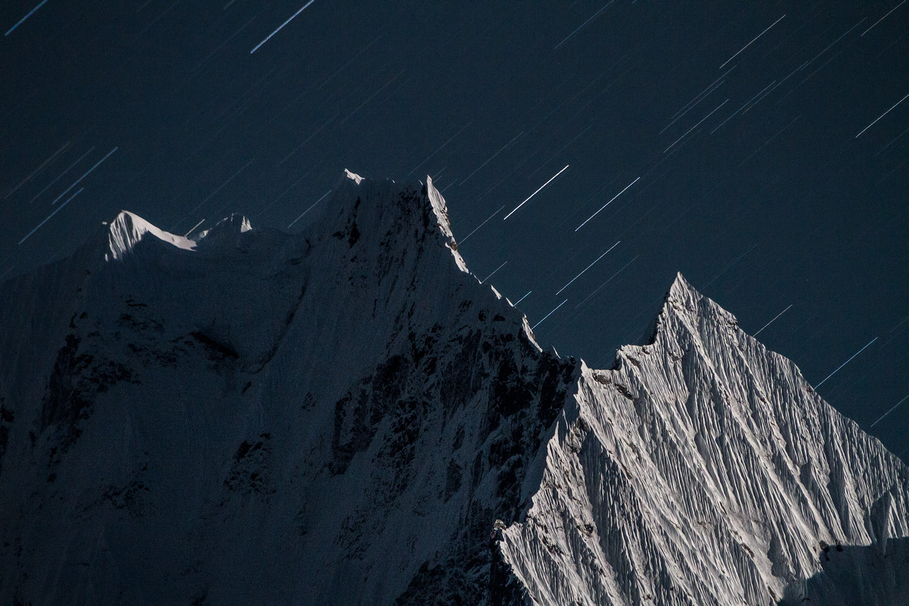 Thamserku at night bathed in moon light with star trails overhead, Khumjung, Nepal