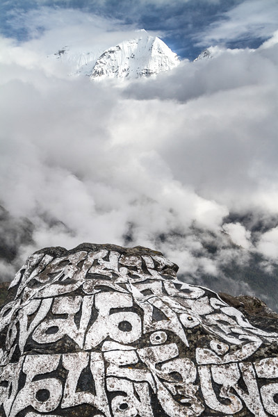 "Carved rocks, called mani stones, display the Buddhist prayer ""Om mani padme hum"" in front of Himalayan peaks and clouds"