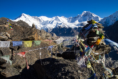 Tibetan Buddhist Prayer Flags hang in a line, attached to a shorten atop Gokyo Ri in Nepal with Cho Oyu, the 6th highest mountain in the world, behind