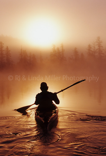 Man Kayaking in Fog at Sunrise