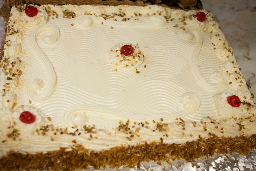 Italian Cream Cake<br /> <br /> A homemade white cake enriched with spice, pecans and coconut. Covered in our homemade Creamy rich Cream Cheese Icing. Decorated with roasted golden coconut on the sides.<br /> <br /> A true favorite for all special occasions.<br /> <br /> Can also be done in rounds or squares. Prices Vary on the size of Cake