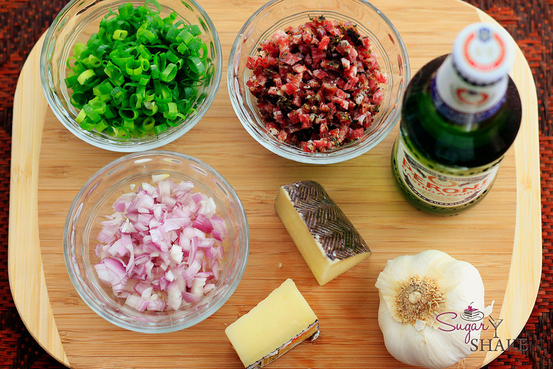 Italian beer bread ingredients (clockwise from upper left): green onions, salami, Peroni Italian beer, garlic, Manchego cheese, shallots. © Sugar + Shake