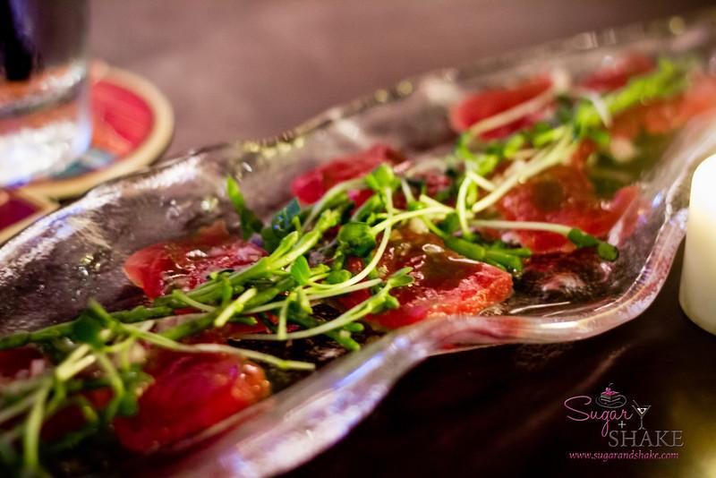New bar menu tasting at Hula Grill Waikiki. Sashimi Hula Style: Raw 'ahi, shallot gremolata, 'alaea salt, Thai basil oil. © 2014 Sugar + Shake