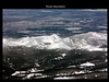 Rocky Mountains from the air.<br /> <br /> Beautiful snow-covered peaks rising about the forested slopes.