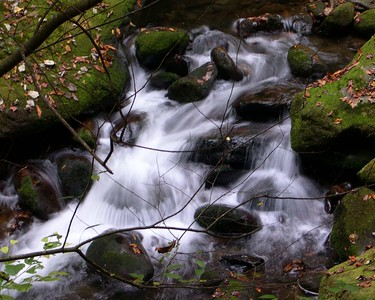 """ROARING CREEK"" Taken outside of Gatlinburg, Tn., 2003 with a Nikon Coolpix 4300.  This effect was created by nature, not me. There were no controls to set shutter speed or the apature on this camera.  Heavy rains caused flooding, and waters coming downhill to run much faster than normal.  That, coupled with the available lightis what made the results possible."