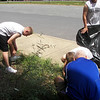 Nicholas, Blanton, and Grigsby help CPT Eldridge weed the flower bed in front of the school.
