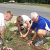CPT Eldridge works with Nicholas and Blanton, weeding the flower bed in front of the school.