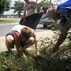 Blanton, and Grigsby help CPT Eldridge weed the flower bed in front of the school.