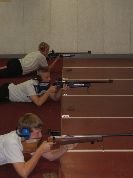 Hower, Nicholas, and Blanton practice their shooting from the prone position.
