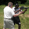 MAJ Blanchetti helps show Okeyo how to hold the weapon correctly on the outdoor range.