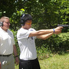 MAJ Blanchetti supervises Liu as he fires a handgun on the outdoor range.