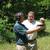 MAJ Blanchetti prepares to take the handgun from Grigsby after his shots are complete.