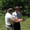 MAJ Blanchetti shows Cafferty how to properly handle a handgun on the outdoor range.