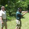 MAJ Blanchetti supervises Cao as he fires a handgun on the outdoor range.