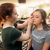 JIM VAIKNORAS/Staff photo Summer Tracy applies makeup to model Paris Bocacum before the Rubbish to Runway Fashion Show at the Governor Academy in Byfield.