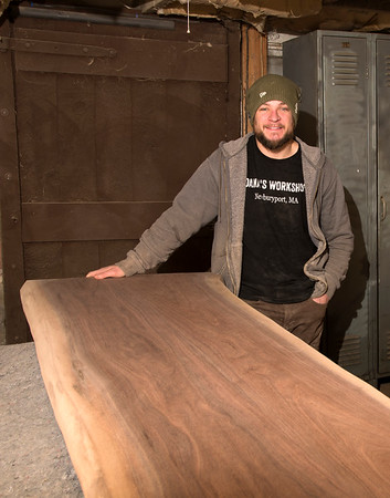 JIM VAIKNORAS/Staff photo Dana Etherington of Dana's Workshop at his basement workshop. He is standing with a commission piece he is making for the Silvaticus Brewery in Amesbury.