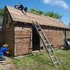 JIM VAIKNORAS/Staff photo Dana Etherington owner of Dana's Workshop, his wife Dana Martin Etherington and friend Eric Brager disassemble a shed.  The shed was at his grandmother house in Newburyport and has provided wood for a number of projects.