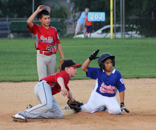 STAN HUDY - SHUDY@DIGITALFIRSTMEDIA.COM Saratoga National Little League base runner Joey Barreto looks up and asks for time after stealing second base as Glens Falls shortstop Cason Rath applies the tag and second baseman Tristan Davila (27) looks on during the District 11 championship game Saturday, July 16, at West Side Rec.