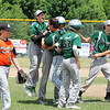 STAN HUDY - SHUDY@DIGITALFIRSTMEDIA.COM<br /> Clifton Park Plainsmen's Ayden Harrison (center) is mobbed by his teammates after delivering two-run single that scored two runs and saw Brady Altobelli score on an error on the play to defeat Marlboro, 8-7, in their final at-bats Saturday during the Cal Ripken Baseball Eastern NY State tournament in Latham.