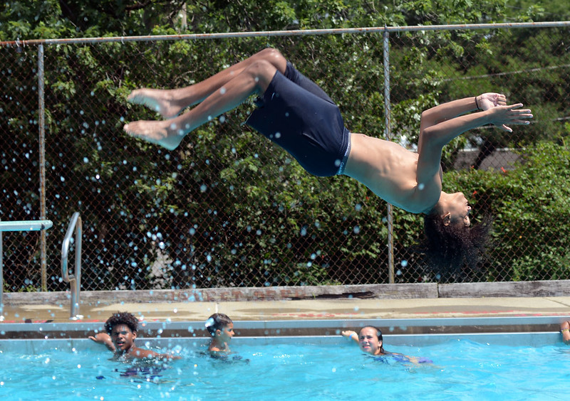 Tania Barricklo-Daily Freeman    Lauren Park summer campers look on as their counselor Daivel Jackson, 17, does a backflip off the diving board at Andretta Pool in Kingston, N.Y. Tuesday afernoon.  Tuesday was the last pool day for the camp and Friday is the last day of camp for area City of Kingston Parks and Recreation summer camps.