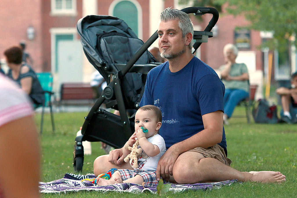. Augusts Concert on the Upper Common in Fitchburg featured De La High a local Latin/ pop group. Listening to the music is Bobby Whitworth of Fitchburg with his son Benjamin, 7 month. SENTINEL & ENTERPRISE/JOHN LOVE