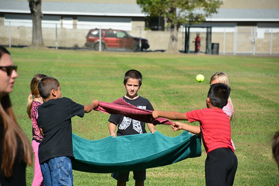 Students Practice Throwing and Catching A Water Balloon With A Towel As A Team.  They Start With A Tennis Ball