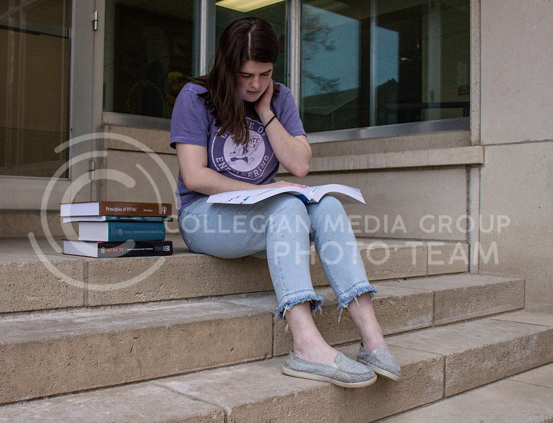 Reading through a building code requirements book, junior in Architectural Engineering Summer Savoy studies on the steps.<br /> Photo by Macey Franko