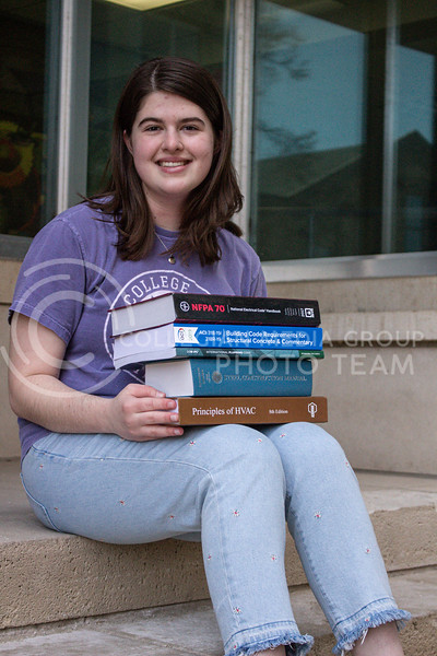 With a stack of textbooks, junior in Architectural Engineering Summer Savoy sits outside of Seaton Hall.<br /> Photo by Macey Franko
