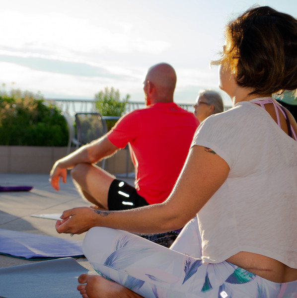Early morning yoga-goers welcome in the longest day of the year by participating in Sunrise Solstice Yoga held on the Flint Hills Discovery Center terrace on June 21, 2018. (Madison Jahnke | Collegian Media Group)