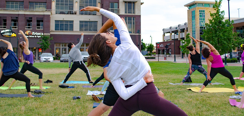 Yogis wrap up the day of the summer solstice at the Blue Earth Plaza by participating in Sunset Solstice Yoga. The hour-long session was instructed by Mitzie Rojas of the Douglass Community Recreation Center on June 21, 2018. (Madison Jahnke | Collegian Media Group)