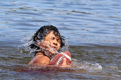 Thurman Hargrove IV of Ayer comes out of the water after diving for a football as he played catch with his dad at Sandy Pond in Ayer on Monday afternoon. SUN/JOHN LOVE