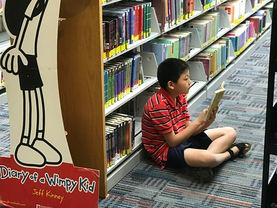 William Shi, of Rochester Hills and a fourth grader at Musson Elementary, sits reading in the Rochester Hills Public Library in downtown Rochester during a visit while his mother, Xie, was with a sibling in the youth section. Photo by Stephen Frye / Digital First Media