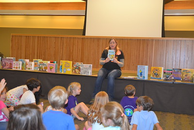 Liz Clauder, a librarian at the Bloomfield Township Public Library, reads to children in the summer reading program. Educators say reading helps children retain knowledge across all academic subjects when they are on summer recess from school. Anne Runkle-The Oakland Press