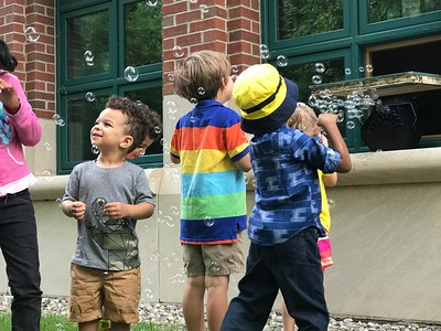 Andrew Hodge, of Rochester, looks up as he and other children finish an outdoor story time at the Rochester Hills Public Library in downtown Rochester with a bubble machine. Summer reading programs vary and emphasize making reading fun. Photo by Stephen Frye / Digital First Media