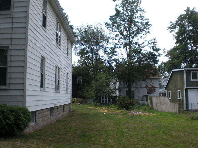 Side yard--the big lilac bush is gone, Aunt Peggy used to grow rhubarb among other things out in that patch at the back and her son Donald lived in one of those houses behind, facing on the next street.