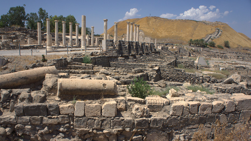 Beit She'an. The hill in the background has traces of civilization to the early second millennium B.C.E. The Roman city in the forebground, was started during the Roman Era and expanded during the Byzantine Period. An earthquake in 738 destroyed the city. Numerous cracked pillars are in view.