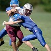 Jackson Arbour, back, and Brandon Giguere of Oak Hill High School tackle Jesse Drury of Foxcroft Academy Saturday in Wales. Daryn Slover/Sun Journal