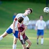 Silas Dumont of Oak Hill High School heads the ball over Brandon Smith of Monmouth Academy during the second half of Wednesday's game in Monmouth. Daryn Slover/Sun Journal