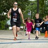 Rick Bourgeois of Greene crosses the finish line Sunday with his children, Sophie and RJ, during the Triple Crown 5K in Auburn. Photo by Daryn Slover/Sun Journal