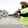 Volunteer Jason Raper of Auburn cheers for runners and walkers Sunday during the Triple Crown 5K in Lewiston. Photo by Daryn Slover/Sun Journal