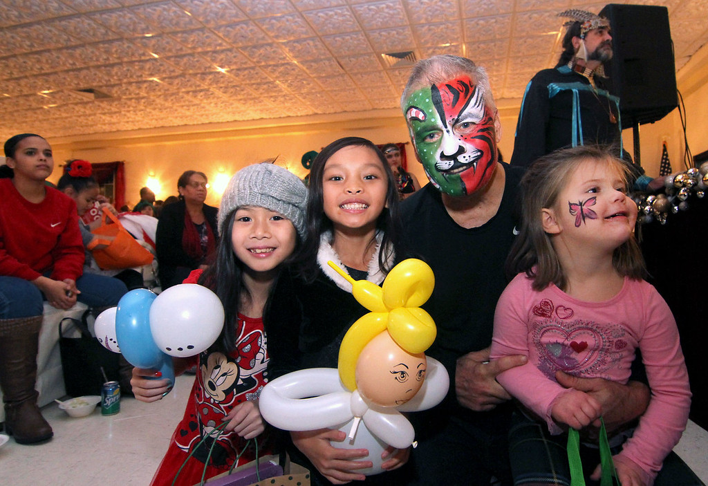 . Enjoying the Native American dancers at the  Enterprise Bank\'s 3nd Annual International Holiday Celebration is L-R, Hope Chanthaseng 8, Soriya Soen 6, and Jack Clancy (CEO/Enterprise Bank), holding his grandaughter Lucy Petro-Roy 4. SUN/ David H. Brow