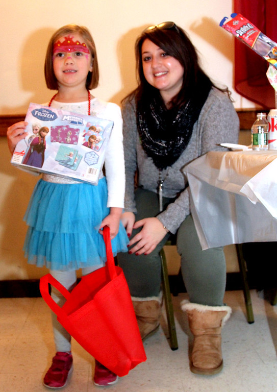 . Showing her prize she just got from the SunSanta raffle table is Ellie Petro-Roy, 5, with Jackie Silva who was working the table at Enterprise Bank\'s 3nd Annual International Holiday Celebration. SUN/ David H. Brow