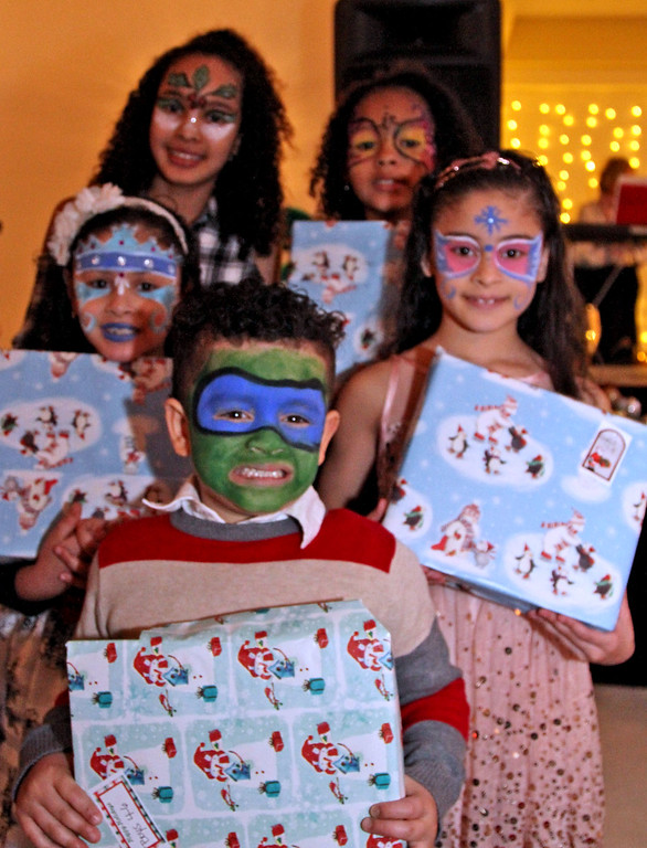 . Holding their gifts just received from Ms&Mrs Santa Claus at the 3nd Annual Enterprise Bank\'s International Holiday Celebration is L-R, front to back, Antonio Cortes,4, Jalexa Cortes, 8, Charleni Zabala,12, Nicauri Zabala,9 and Jelexa Cortes, 9, all from Lowell. SUN/ David H. Brow