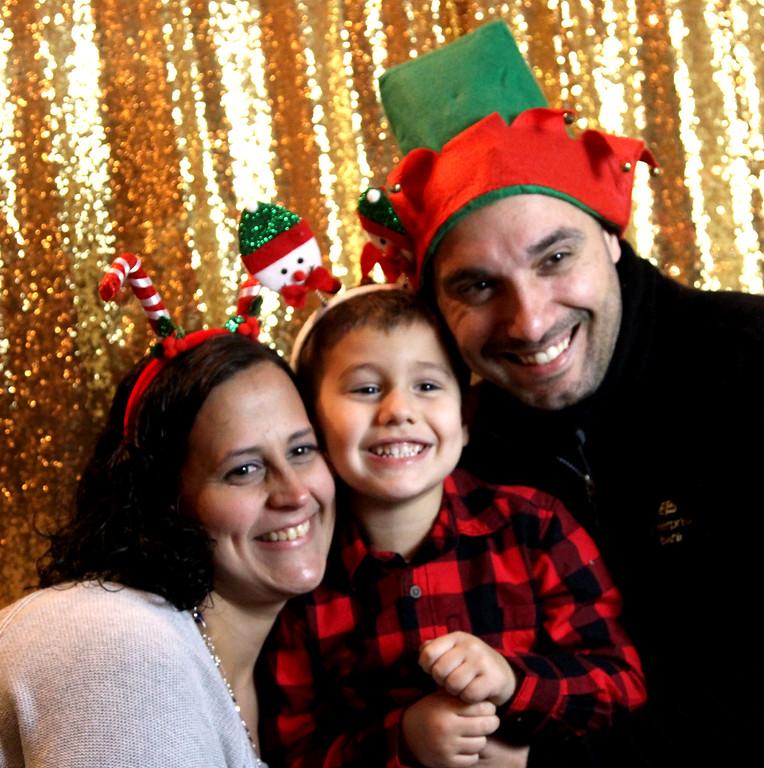 . Having a holiday family photo taken at the Enterprise Bank\'s 3nd Annual International Holiday Celebration is Nancy Moniz, Austin Moniz 4, and Michael Moniz (Enterprise employee), the family is from Methuen. SUN/ David H. Brow